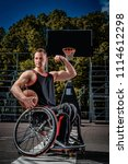 Small photo of Smiling cripple basketball player in wheelchair holds a ball on open gaming ground.