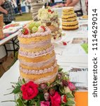 Small photo of A row of summer cakes line up for judging at a cake competition at a traditional english country fete.