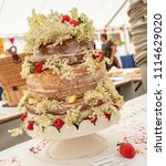 Small photo of A multi-tiered sponge cake with vanilla icing decorated with summer flowers and strawberries, awaits judging at a traditional english fete.