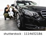 Small photo of Car detailing - Worker with orbital polisher in auto repair shop. Selective focus.