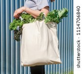 Small photo of Plain flex eco-bag with green fresh kale and arm on the background of the metal fence or wall