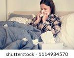 sick woman sneezing in bed | Shutterstock . vector #1114934570