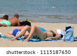 sunbathers enjoying the beach | Shutterstock . vector #1115187650