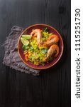 Small photo of Spanish paella with seafood on the red teralke with lime. Delicious lunch on the shore of the sea shrimp. Dark wood background