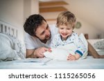 father with toddler boy reading ... | Shutterstock . vector #1115265056