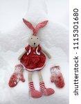 a toy rabbit walks in a snowy... | Shutterstock . vector #1115301680