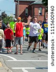 Small photo of Fairhaven, Massachusetts, USA - June 17, 2018: High-five from a spectator at the Fairhaven Father's Day Road Race