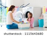 mother and kids in laundry room ... | Shutterstock . vector #1115643680