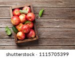 Ripe red apples in wooden box....