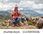 Stock photo the old man quechua dressed in a colored poncho and a cap of chullo sits on the rocks with a view 1115855036