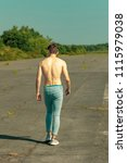 Young adult male walking away with no shirt on on a warm summer's day - stock photo