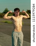 Young adult male flexing his muscles shirtless on a warm summer's day - stock photo