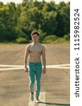 Young adult male walking forward shirtless on a warm summer's day - stock photo