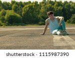 Young adult male sitting outside in the sun - stock photo