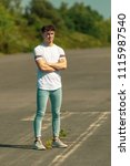 Young adult male standing outside in the sun - stock photo