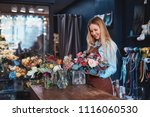 smiling florist with bouquet at ...   Shutterstock . vector #1116060530