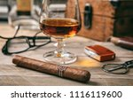cuban cigar and a glass of... | Shutterstock . vector #1116119600