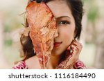 hindu bride holds autumn leaf... | Shutterstock . vector #1116184490