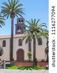 Small photo of Tenerife, Canary islands - june 19, 2018: Gardens with palm trees and facade of the Concepcion church, with the bell tower in the background, in the urban center of the city of La Laguna