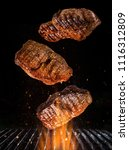 tasty beef steaks flying above... | Shutterstock . vector #1116312809