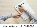 kid holding pen and writing in... | Shutterstock . vector #1116390500