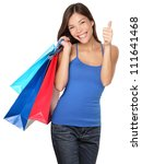 Shopping woman showing thumbs up success holding shopping bags isolated on white background. Beautiful young mixed race Asian Caucasian female shopper. - stock photo
