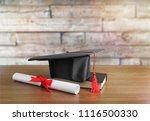 graduation black hat on desk | Shutterstock . vector #1116500330