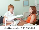 Mature doctor and pregnant woman in clinic - stock photo