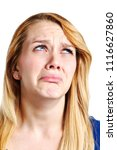 Small photo of A desperately unhappy young blonde woman looks up and sideways, fowning in utter misery.