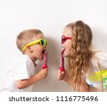 Small photo of Summer sweets for children: Children boy and girl in sunglasses and colored T-shirts eating pink home ice cream on white background. Portrait.