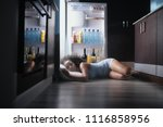 Small photo of Young hispanic woman suffering for summer heat and lack of air conditioning at home. Black girl covered with sweat sleeping on floor with head inside fridge.