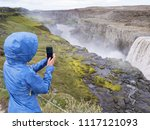 woman in a blue raincoat makes... | Shutterstock . vector #1117121093