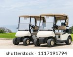 Two empty white golf carts parked beside each other on the driveway of a golf course in Montego Bay, Jamaica.