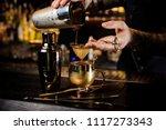 Stock photo bartender with tattoo pouring fresh and tasty summer drink from shaker into the vintage copper mug 1117273343