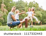 father plays and rocks with... | Shutterstock . vector #1117332443