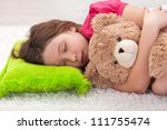 Young girl taking a peaceful nap with her favorite teddy bear - stock photo