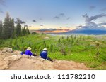 Senior couple hikers are watching sunset in  firled of wild flowers and ocean. Mt. Rainier national Park area. Naches Peak Loop Trail. Roundtrip 3.0 miles, Elevation Gain 600 ft Highest Point 5849 ft - stock photo