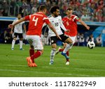 Small photo of St Petersburg, Russia - June 19, 2018. Egyptian football star Mohamed Salah against Russian players Denis Cheryshev and Sergei Ignashevich during World Cup 2018 match Russia vs Egypt.