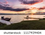 Small photo of Colorful sunset sunrise on a lake. Dock with fishing boat, and a pier with a bench jut into the water. Concepts of vacation travel, resort, weekend getaway