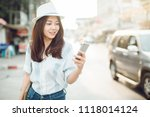 woman walking and using a smart ... | Shutterstock . vector #1118014124
