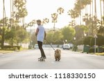Stock photo young man looking back and smile riding on skateboard with puppy chow chow on a street with palm 1118330150