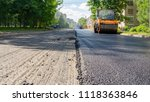 Small photo of Repair works on laying the asphalt surface on a city street. Steamroller machine for laying asphalt