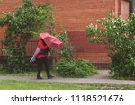 Small photo of A strong gusty wind in the city. Man is opposed to the elements. Bending trees, a hurricane.