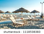 Small photo of Umbrellas and chaise lounges on the beach of Rimini in Italy