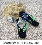 hat and flip flops on the beach   Shutterstock . vector #1118557280