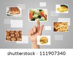 Woman hand uses touch screen interface with food on grey backround - stock photo