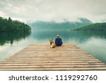 Man With Dog Sitting At Wooden...