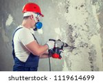 the builder with hammer drill... | Shutterstock . vector #1119614699