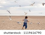 Small photo of baby boy in striped sailor t-shirt running on the sandy beach with seagulls near the sea in summer