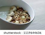 muesli with yoghurt and banana... | Shutterstock . vector #1119644636